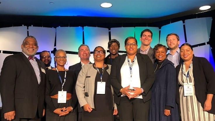 Photo of Mass CultivatED founder Chynah Tyler (in white shirt and black blazer) surrounded by representatives from the Urban League of Eastern Massachusetts, Sira Naturals, the Commonwealth Dispensary Association, MedMen, NETA, the Massachusetts Association of Community Colleges, Roxbury Community College and Smith, Costello & Crawford.